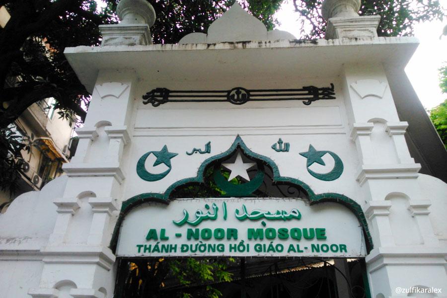 Gerbang utama Masjid Al-Noor dengan tulisan dalam tiga bahasa